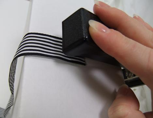 Flip the stapler open and secure the ribbon into the door