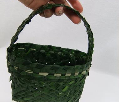 Weaving a diagonal green grass basket