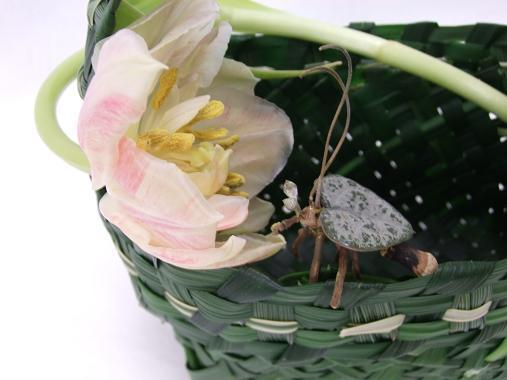 Pine and twig love bug on a green grass hand basket