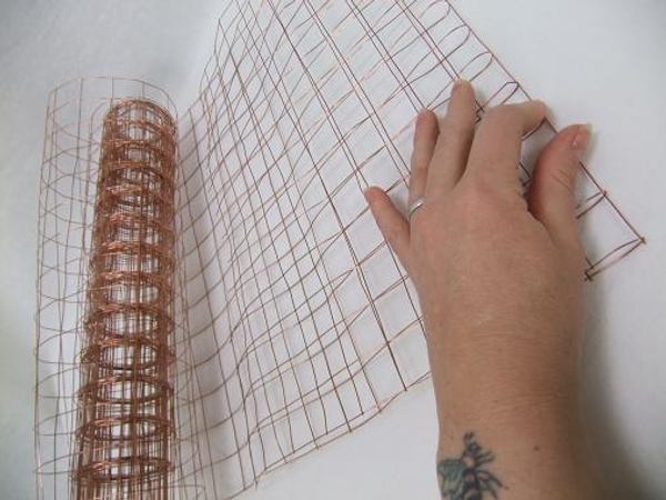 Fold a section of biodegradable copper mesh in half.