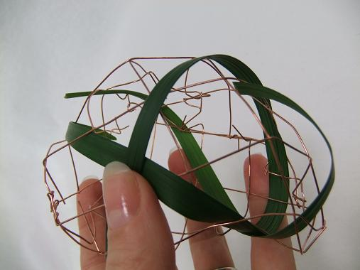 Continue to weave the grass through the biodegradable copper mesh.