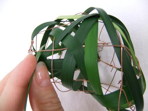 Use the thicker side of the blade of grass to thread it through the wire mesh.