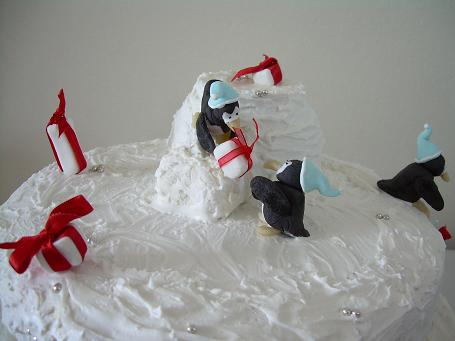 Fondant penguins stacking gifts.
