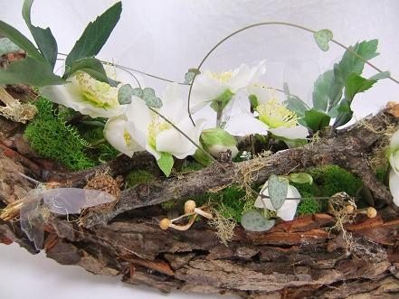 Again Reindeer moss, Hellebore flowers, Lichen covered twigs, Rosary vine and dried mushrooms decorate the design
