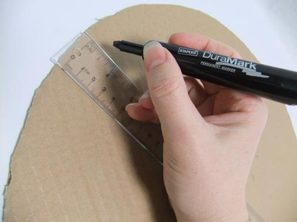 Draw a line about a ruler width right through the middle of the cardboard circle