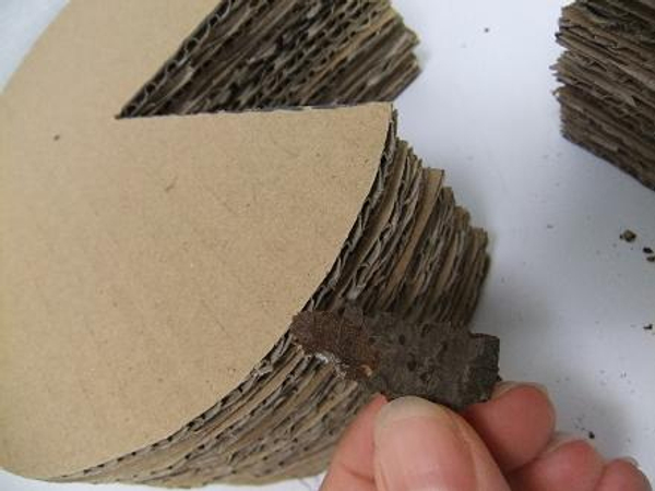 Glue chips of bark to the cardboard stack
