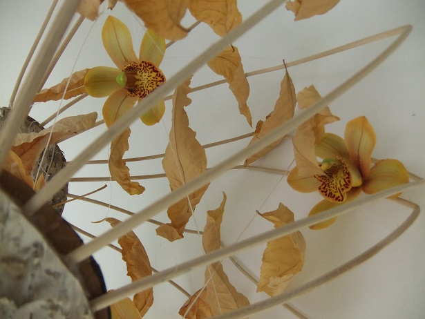 Display Cymbidium orchids and autumn leaves in a handmade basket
