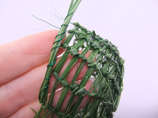 Fold the strands of grass and wire to the side and wrap the next wire around the strands