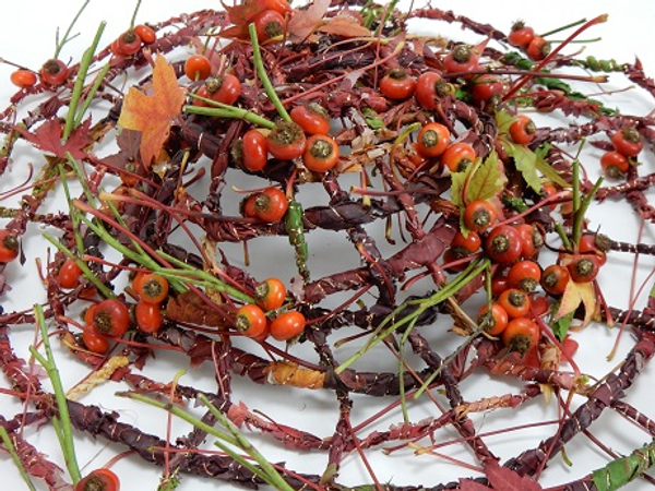 Weaving a hat with an autumn leaf and rose hip garland