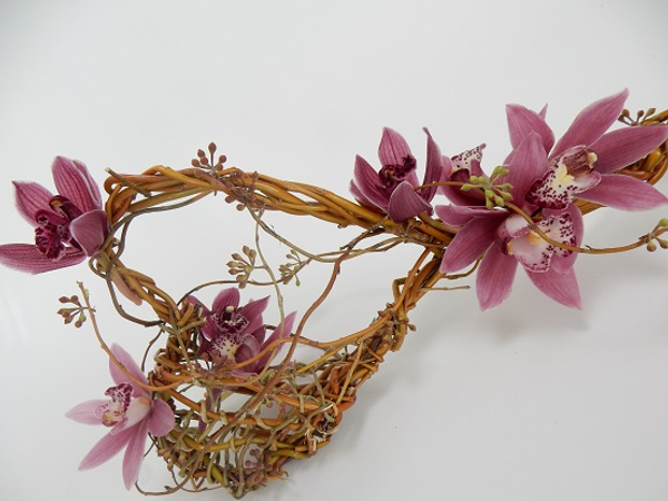 Cymbidium orchids, eucalyptus capsules woven into a willow wand