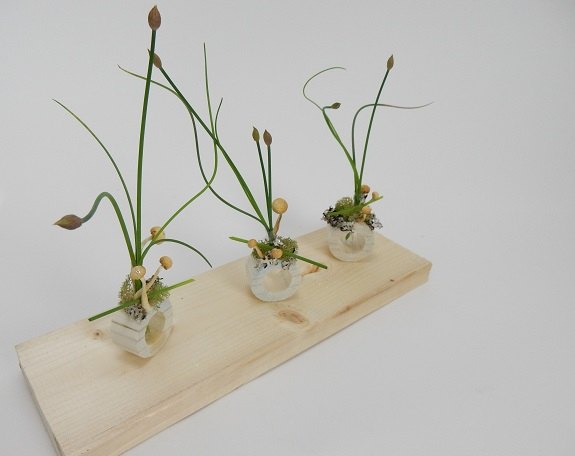 Chive flower heads with moss lichen and mushrooms in a dowel stick container