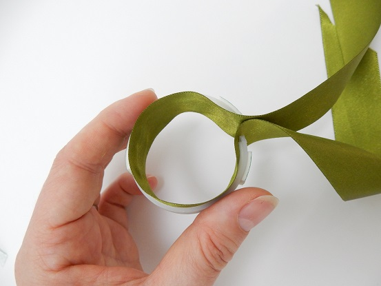 Open the ribbon and start to glue the middle point of the ribbon to the inside middle of the loop.