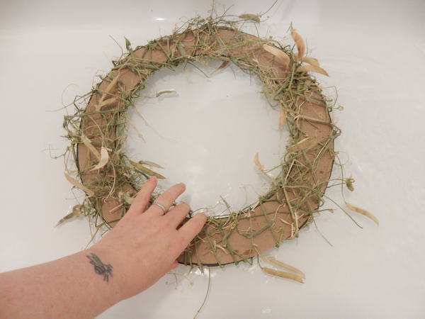To remove the cardboard soak the wreath in a water bath