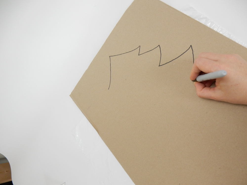 Draw a large Christmas tree shape on cardboard