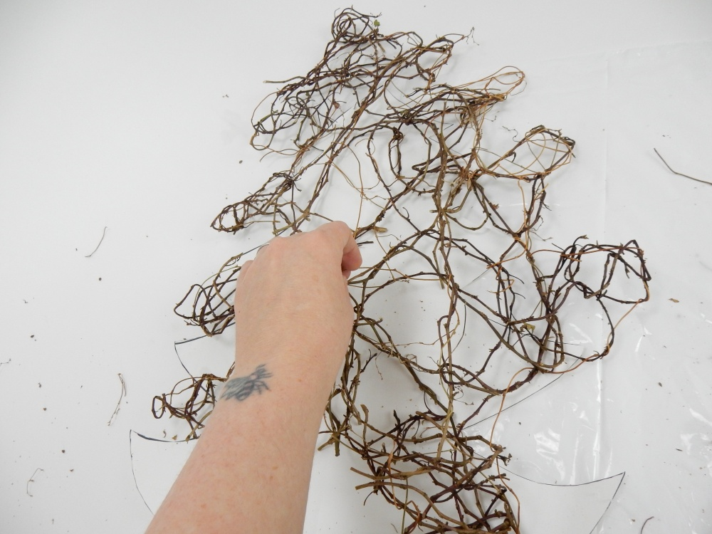 Weave in fresh vine to fill in any gaps to complete the Christmas tree shape
