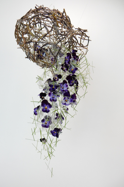 Flowers spilling from a twig vase
