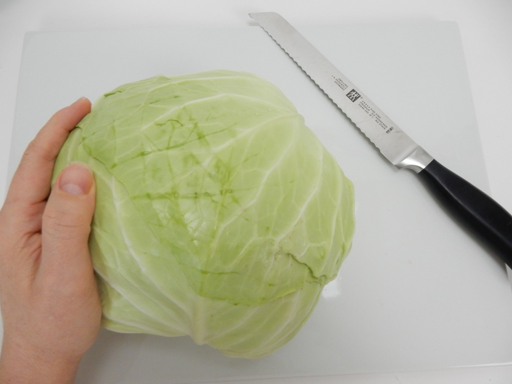 Let the cabbage rest on a working surface to find it's natural balance point