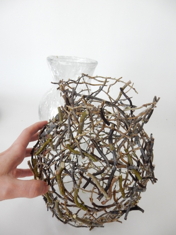 Lift the twig shape away from the vase.