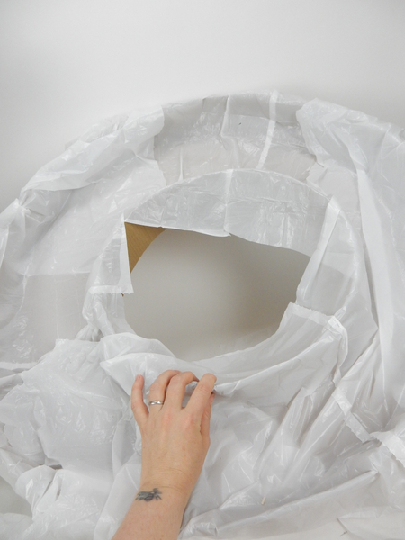 Line the cardboard wreath shape with a thin layer of plastic