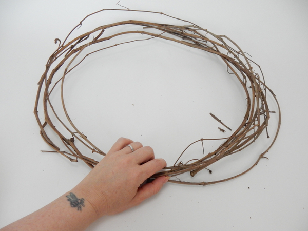 Place a dried vine wreath on a flat working surface