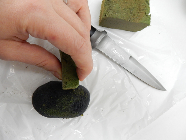 Smooth the soaked foam with an off cut of green foam to give it a mossy appearance