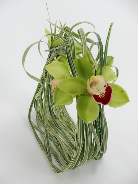 Cymbidium orchids and curled grass with crystals on a basket