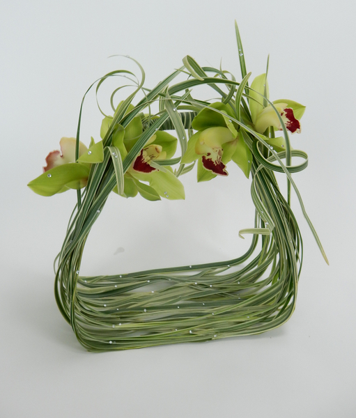 Cymbidium orchids and curled grass with crystals on a bridal basket