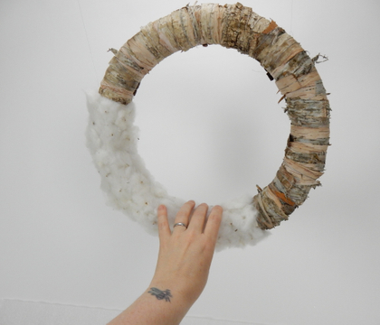 A bark strip and fluffed cotton disk wreath
