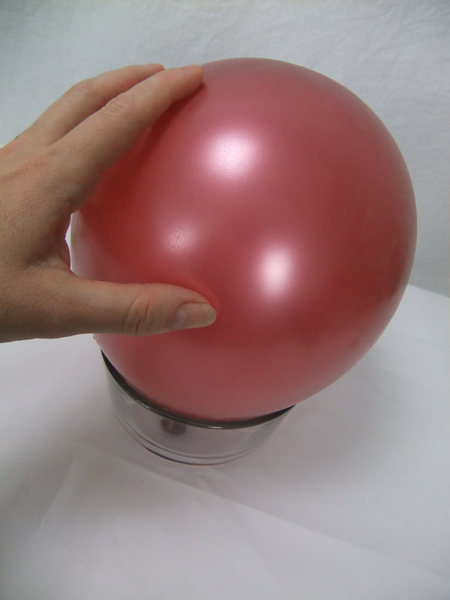 Set the balloon on a small bowl so that it doesn't roll around while you work