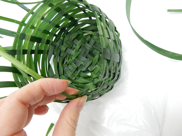 To end the weave fold each strand of grass either over or under the garland strand
