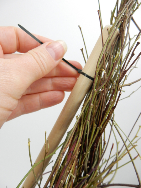Secure the twig bundle to the stick with cable ties
