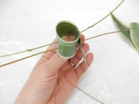Skewer leaf rolls to support a tiny water source for fresh flowers