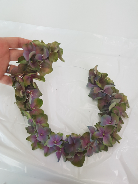 Lift the hydrangea wreath and gently wiggle it.  Glue down any florets that are not secure.