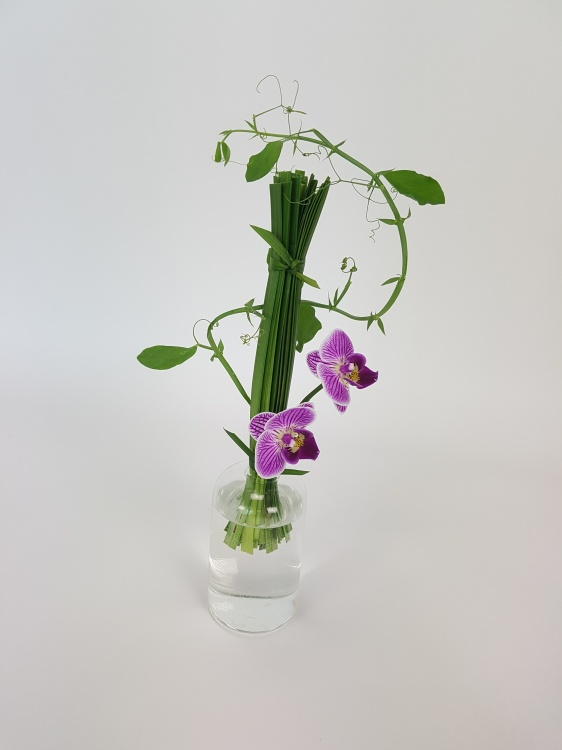 Phalaenopsis, lily grass and sweet pea flower arrangement