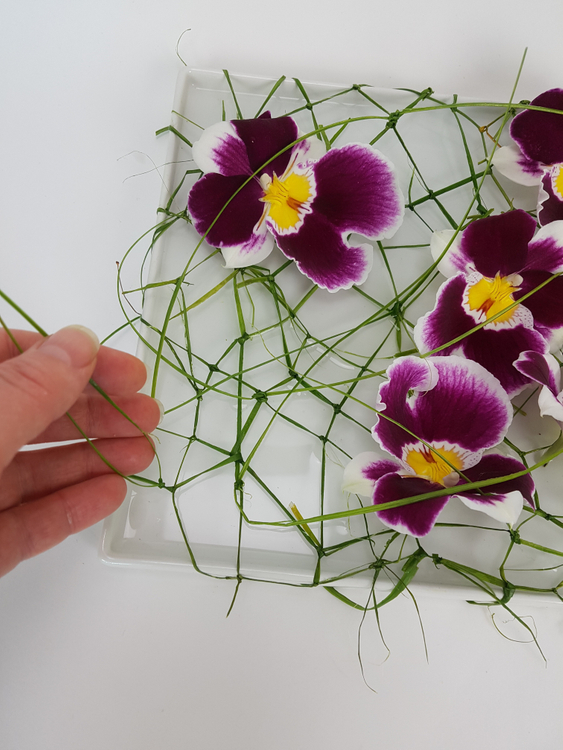 Set your flowers in the shallow container.  The flower stems should be in water and the flower resting above the water on the knotted net of ripped grass.