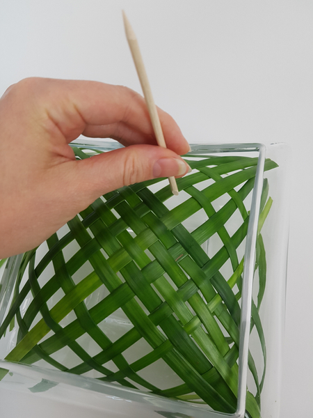 Spread out the woven blades of grass to fill the opening of the container.