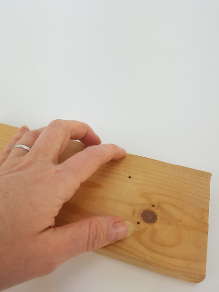 Drill a small hole in a piece of lumber