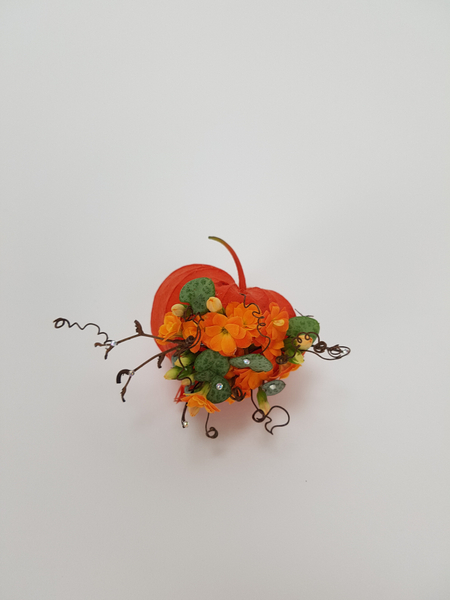 Kalanchoe and rosary vine in a Physalis pod floral art design