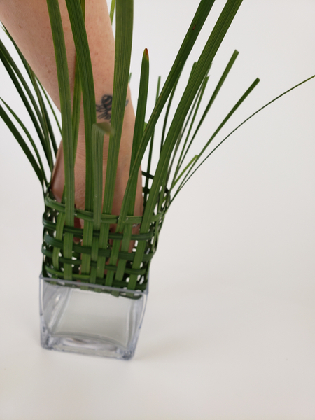 Set the grass into the larger glass container