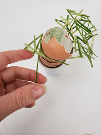 An eggshell stack and grass snippet arch with a hidden water source for a Spring or Easter design