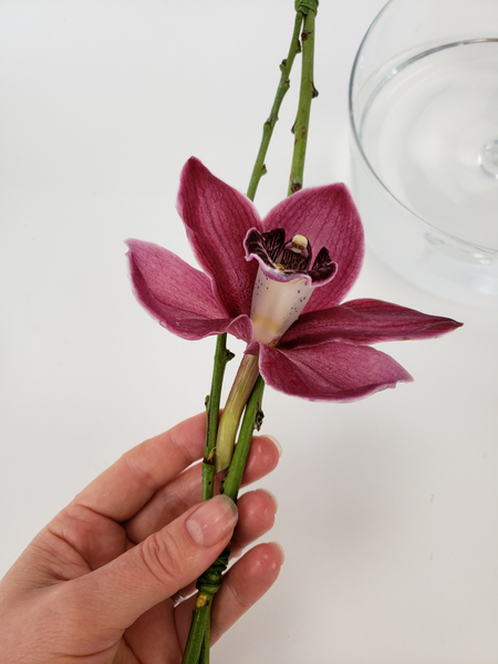 Slip the flower between the two twigs so that it is wedged into place