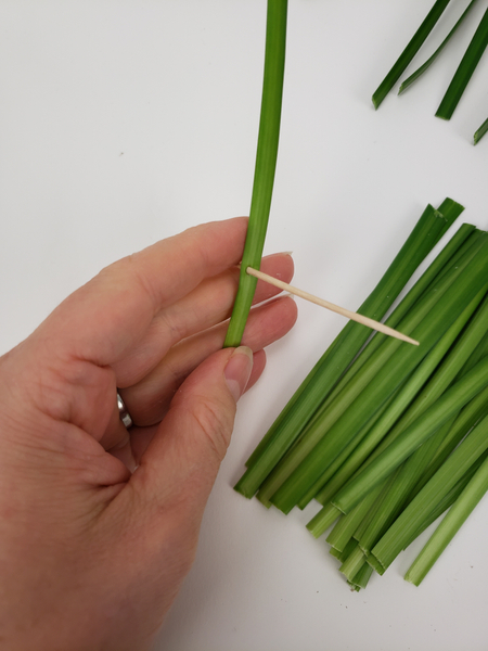 Make a hole in the grass with a sharp bamboo stick