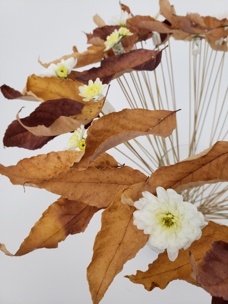 Creative way to display foraged autumn leaves in a floral design