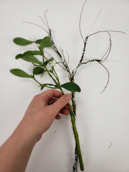 Place the stems on a flat surface and add the mistletoe