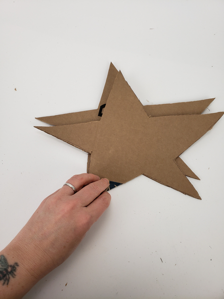 Cut out two cardboard star shapes