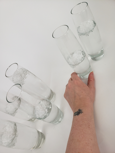 Pour water into the bud vases so that the snow floats