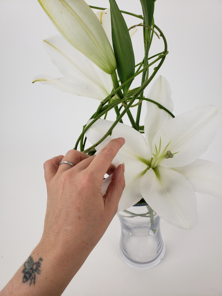 Tuck in another lily low into the vase at the back
