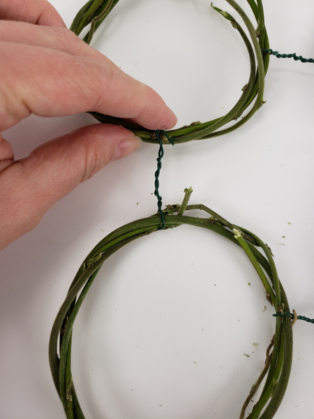 Twist the wire around the partner wreath and fold in the ends