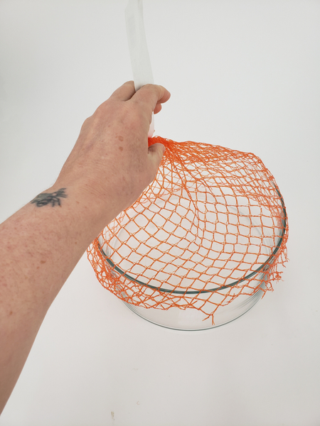Wrap the net over the opening of a container