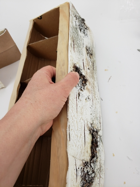 Fit the bark to the side of the paper log and glue down with a generous amount of hot glue
